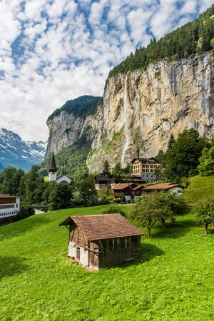 Amazing view of famous Lauterbrunnen town in Swiss Alps valley with beautiful Staubbach waterfalls behind, Switzerland.