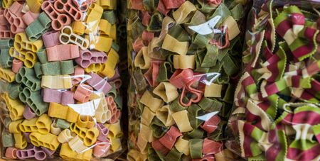 Verities of colorful pasta packed in plastic bags
