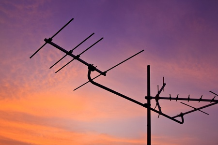 Silhouetted of a television antenna with morning light photo