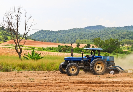 The blue tractor working on a field photo
