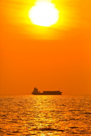 Silhouette of cargo ship with sunset photo