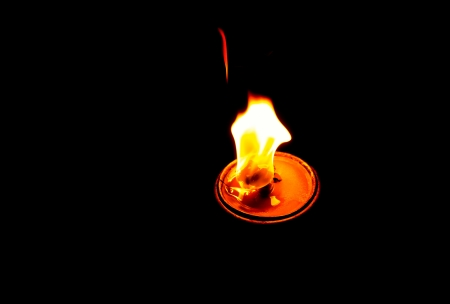Flame of an oil lamp in black background
