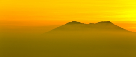 Silhouetted of mountain in mist with morning light photo