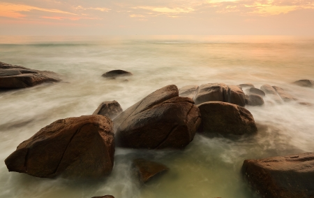 Long exposure of sea and rock in evening Stock Photo