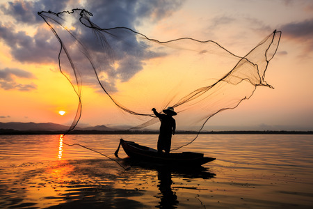 silhouetted: Silhouetted of a fisherman in the morning on the lake Stock Photo