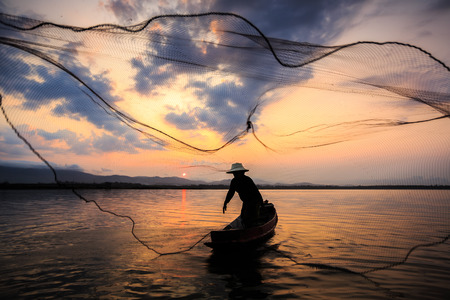 entrapment: Silhouetted of a fisherman in the morning on the lake Stock Photo