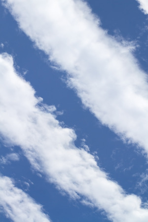 Striated white clouds on blue sky