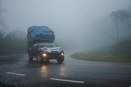 Small truck driving on the foggy road