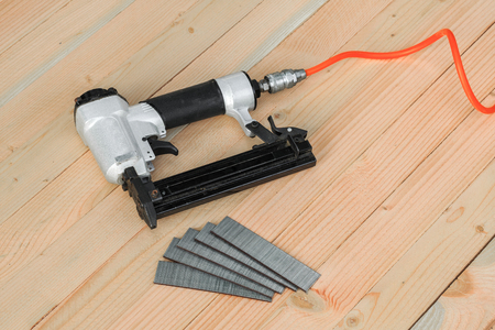 Air nailer tool on wooden board Imagens