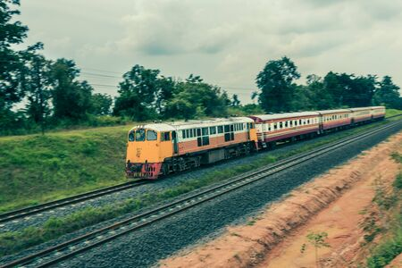 Passenger train running on the railway with rural view