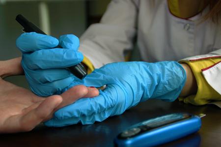 Female doctor puncturing a finger for blood sugar level test