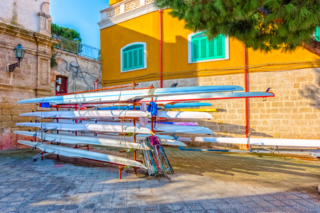 Racing rowing boats standing on metal stand at Monopoli old port. Stock Photo