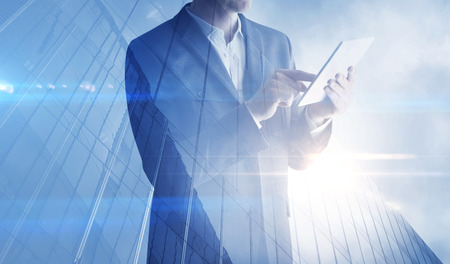 executive job search: Double exposure of skyscraper and businessman with digital tablet