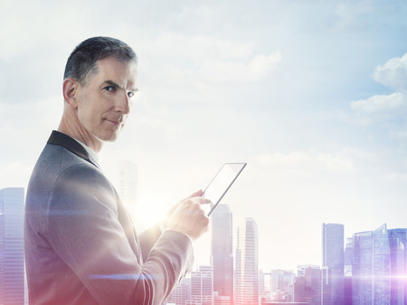 Businessman with digital tablet and blurred city on horizon Stock Photo
