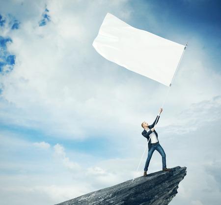 persona de pie: Hombre con bandera en blanco que se coloca en la parte superior de una roca