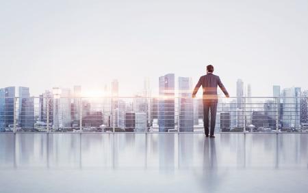 hombre de negocios: El hombre de negocios de pie sobre un techo y mirando al atardecer Foto de archivo