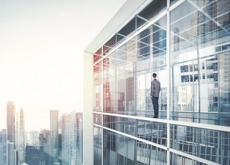 Businessman inside the house looking at city