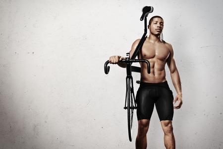 hombre deportista: Atleta joven con la bicicleta Foto de archivo