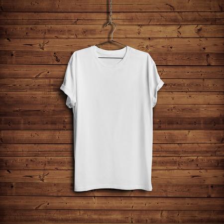 camisas: Camiseta blanca en la pared de madera Foto de archivo