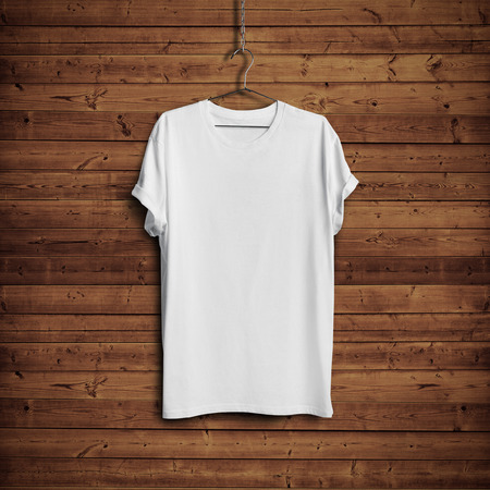 up: White t-shirt on wood wall Stock Photo