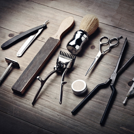 Vintage equipment of barber shop on wood background photo