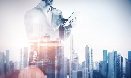 exposición: Doble exposición de una ciudad y hombre de negocios con tableta digital