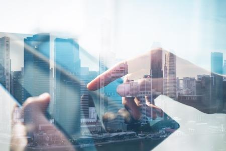 Dubbele belichting van stad en handen met behulp van een tablet