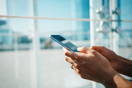 sms: Girl using her smart phone for text sms Stock Photo