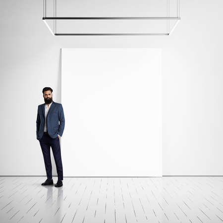wall bricks: Youn bussines man wearing casual suit and blank poster on a wall in the modern interior Stock Photo