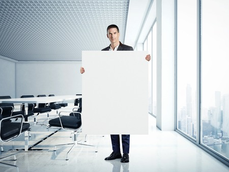 blank canvas: Business man holding white blank canvas at modern office Stock Photo