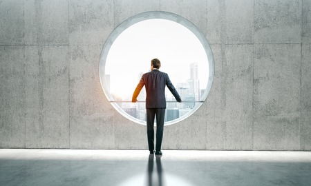 bussinesman: Blank space interior with view on the city and yound bussinesman wearind modern suit