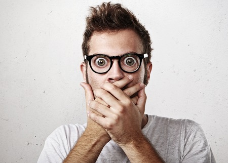 mouth  open: Portrait of a surprised young man wearing eyeglasses
