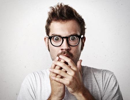 asustado: Retrato de un sorprendido j�venes anteojos hombre que llevaba