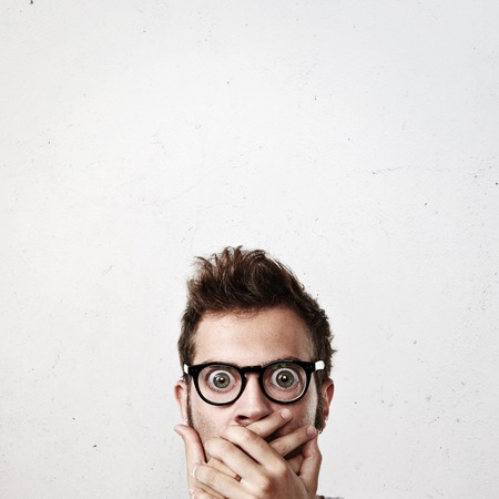 face expressions: Portrait of a surprised young man wearing eyeglasses