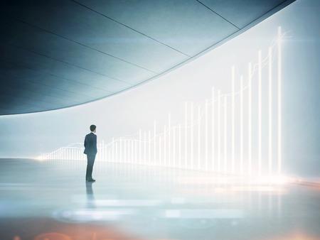hombre de negocios: Hombre de negocios que mira el gráfico en pantalla holográfico