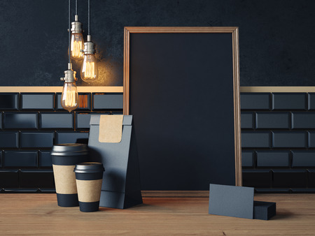 Black poster on table with black coffe cups, business cards and vintage lamps