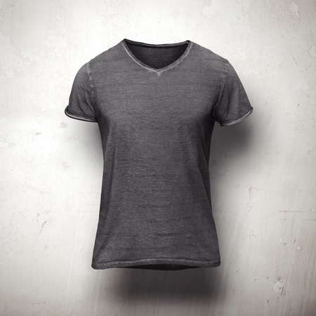 Dark grey t-shirt isolated on grey wall Фото со стока