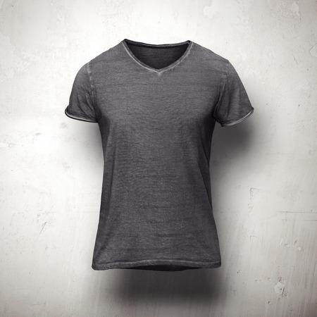 llanura: Oscuro Camiseta gris aislado en la pared gris