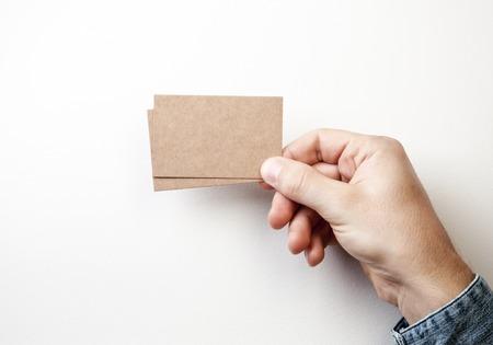 Hasta simulacro de dos tarjetas de visita kraft blanco que sostiene en una mano sobre el fondo blanco Foto de archivo - 43836225