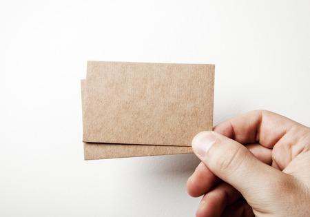 Burlarse de dos tarjetas de visita en blanco en una mano Mans en el fondo blanco Foto de archivo - 43838622