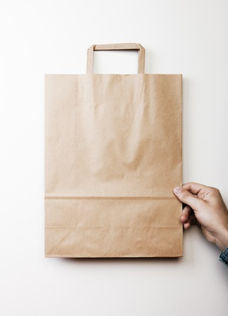 craft paper: Mock up of blank craft paper bag holding in a hand on the white background