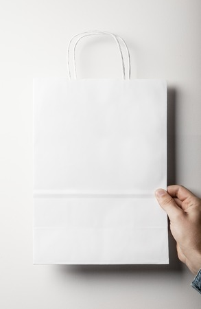 paper bag: Mock up of blank white paper bag holding in a hand on the white background
