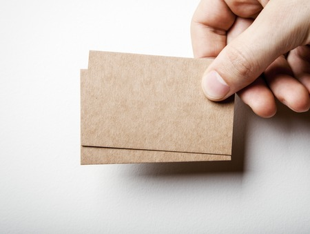 Mock-up van twee lege kraft visitekaartjes deelneming in een mans hand op de witte achtergrond