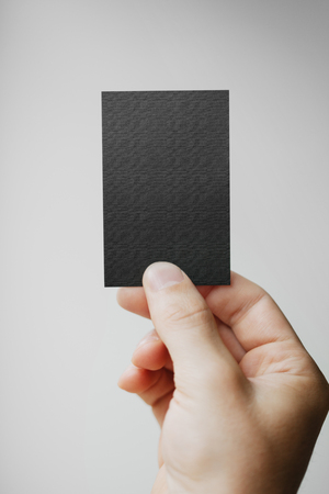 vertical: Hand holding business card on blurred background