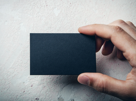 business in hand: Hand holding business card on wall background
