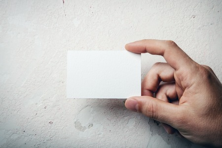 Hand holding business card on wall background