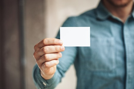 hand with card: Man holding business card on blurred background Stock Photo