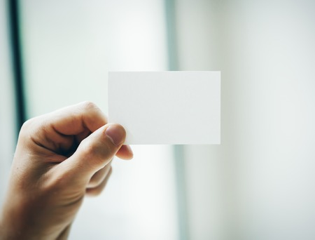up: Hand holding business card on blurred background