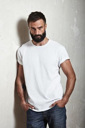 Portrait d'un mec barbu portant t-shirt blanc