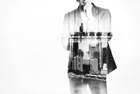 businessman suit: Double exposure concept with thinking business man and city on the background